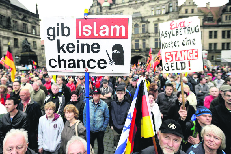 A demonstrator holds a sign that says: u2018Give No Chance to Islam,' at a rally organized by PEGIDA before the elections in Dresden on 7 June.