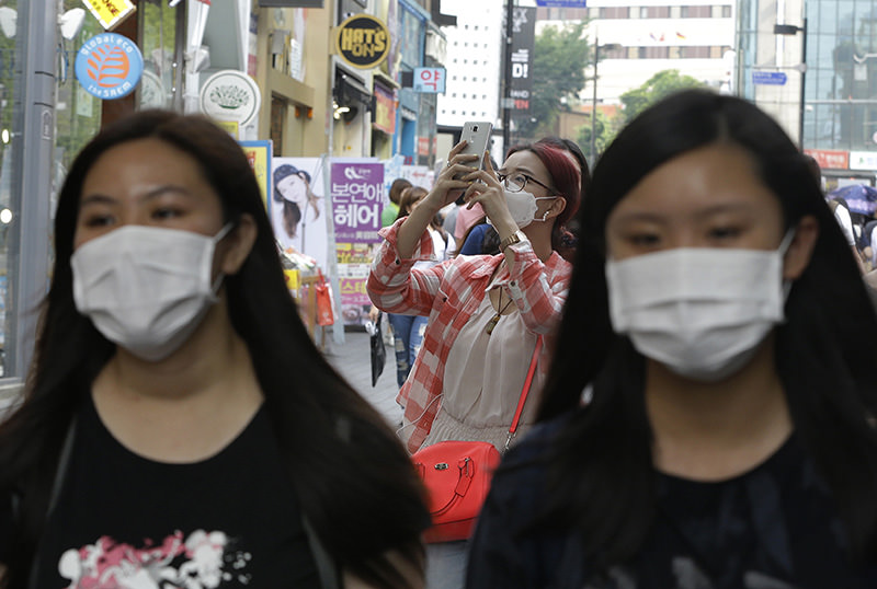 A foreign tourist, center, wears a mask as a precaution against Middle East Respiratory Syndrome (MERS) in Seoul, South Korea, Monday, June 8, 2015 (AP Photo)