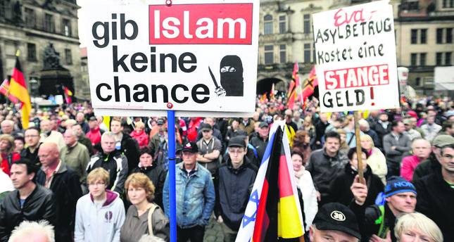 A demonstrator holds a sign that says: 'Give No Chance to Islam,' at a rally organized by PEGIDA before the elections in Dresden on 7 June.