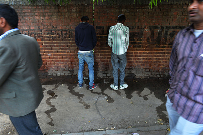 Indian men urinate on a wall at the roadside in New Delhi, the eve of World Toilet Day (AFP Photo)