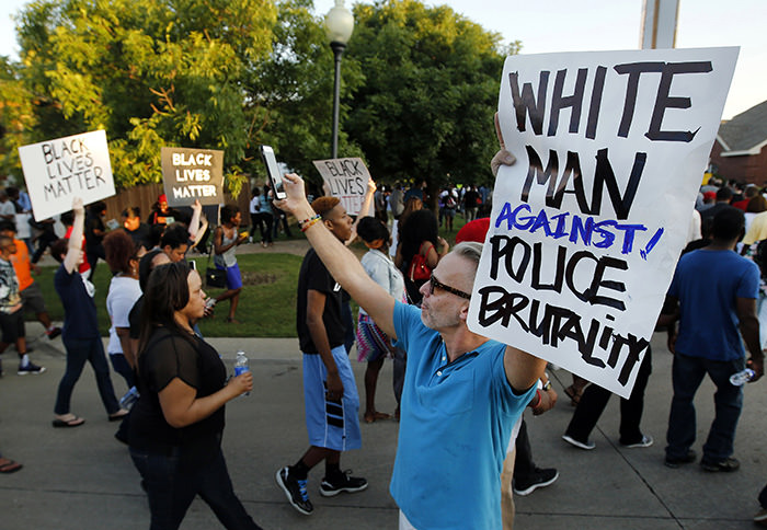 Todd Whitley, center, of Hope for Peace and Justice showed his support for protestors that marched outside the Craig Ranch pool Monday, June 8, 2015. (AP Photo)