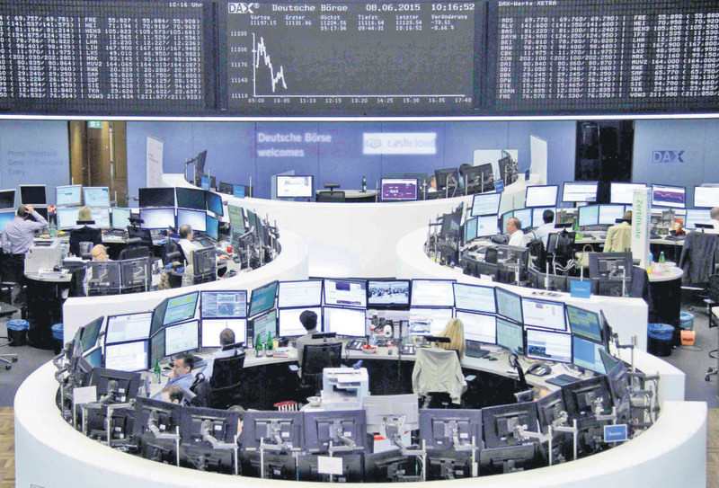 Traders work at their screens in front of the German share price index DAX board at the stock exchange in Frankfurt.