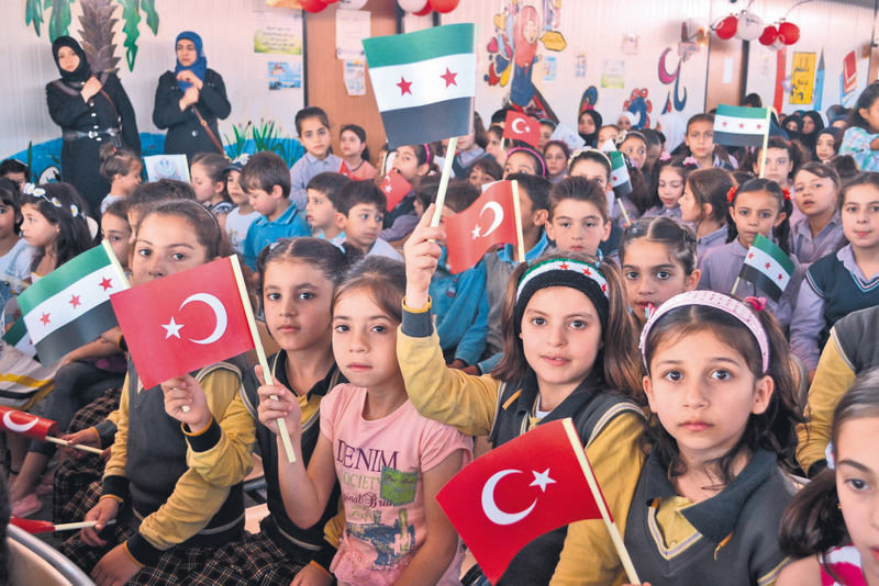 Young Syrian students at a school for refugees waving Turkish and Syrian flags at an event on June 1 in the southern city of Hatay.