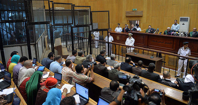Egyptian defendants sit behind bars as journalists attend their retrial over a 2012 stadium riot in the canal city of Port Said that left 74 people dead on May 30, 2015 at the police academy in Cairo. (AFP Photo)