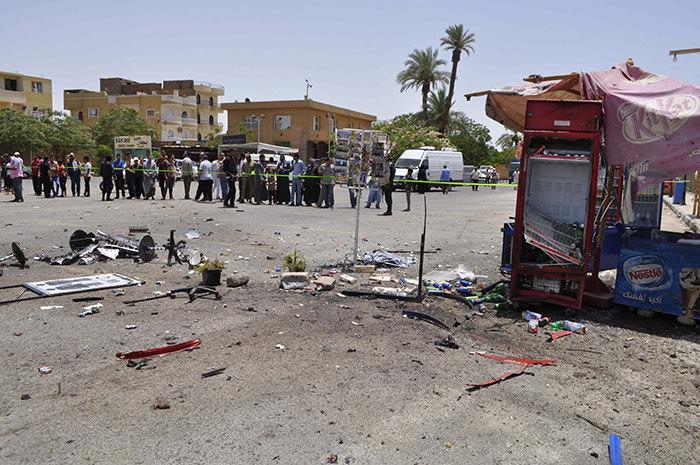 A crowd looks on at the site of a suicide bombing, near Karnak Temple in Luxor, Egypt, Wednesday, June 10, 2015 (AP Photo)