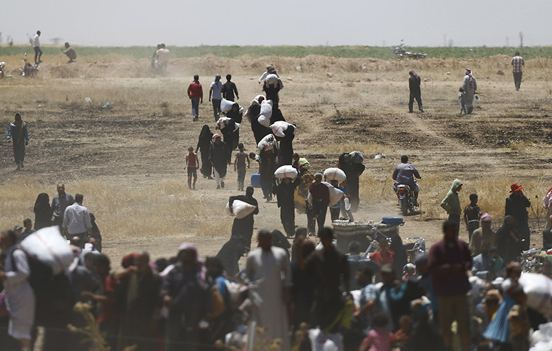 Syrian refugees wait behind the border fences as they are pictured from the Turkish side of the border, near Akcakale in Sanliurfa province, Turkey, June 10, 2015 (Reuters Photo)