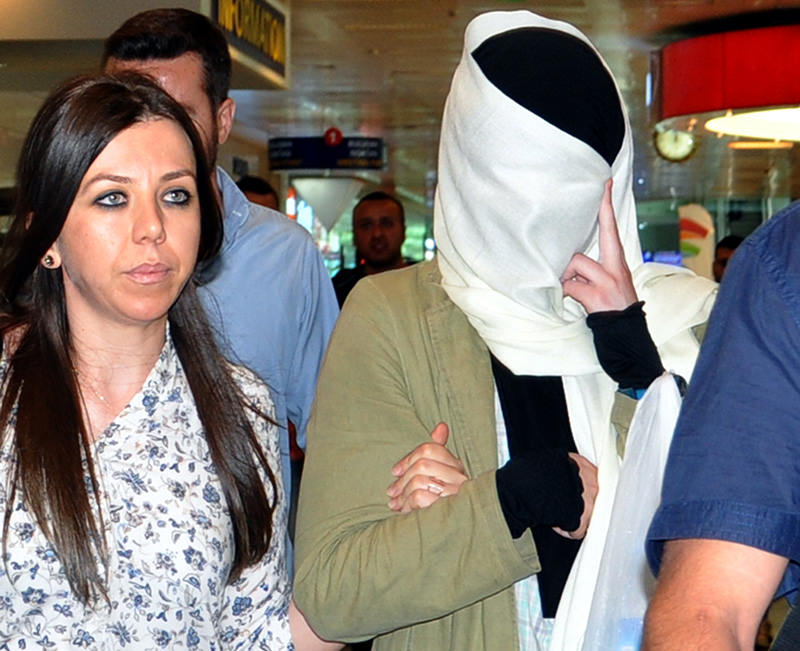 Karaulova concealing her face with a scarf to prevent press members from taking her picture at Istanbul Ataturk Airport, on June 11, 2015 (AA Photo)
