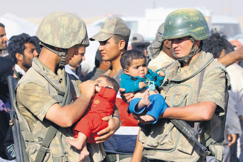 Turkish soldiers patroling the border with Syria help refugees entering the country on Thursday as clashes rage in the city of Ras al-Ayn.