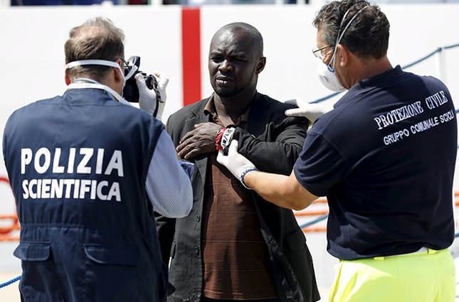 Italian police takes a photo of a rescued migrant with his identification number after he disembarked at the Pozzallo harbour, Italy, June 9, 2015 (Reuters Photo)