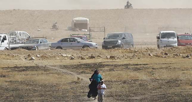 Syrian refugees walk towards border fences as they are pictured from the Turkish side of the border, near Akçakale in Şanlıurfa province, Turkey, June 10, 2015 (Reuters Photo)