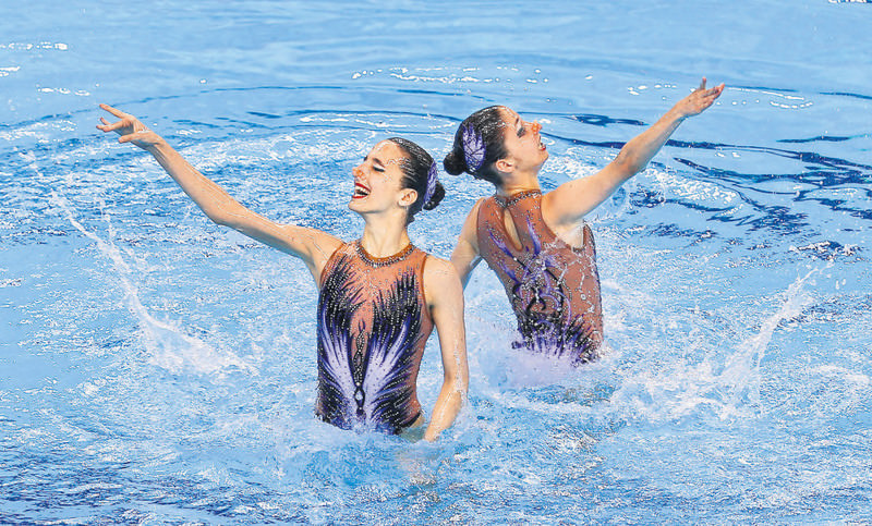 Austria's swimmers Anna-Maria Alexandri and Eirini-Marina Alexandri perform during the Synchronised Swimming Duets Qualifications Free Routine at the Baku 2015 European Games.