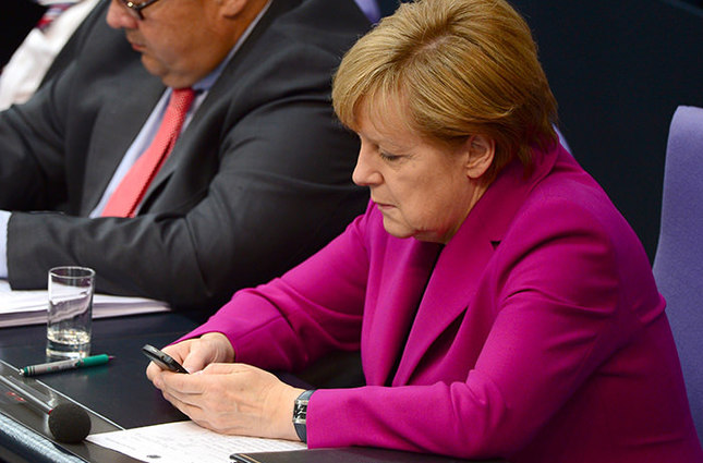German Chancellor Angela Merkel (R) reading her mobile phone during a session of the Bundestag Lower House of parliament in Berlin (AFP Photo)