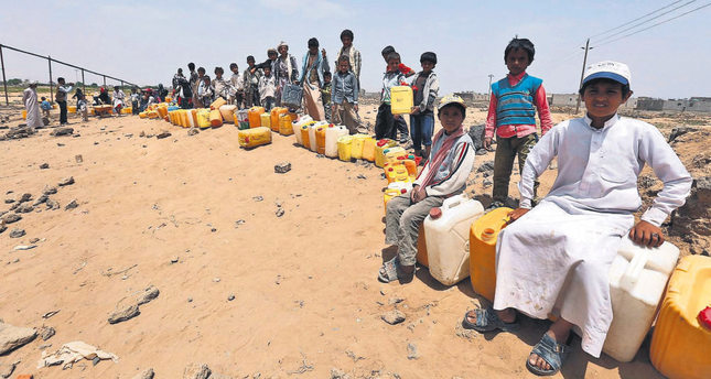 Yemeni children wait to fill jerry cans with water from a source donated by a benefactor amid ongoing disruption to water supplies in Sana'a on June 6.