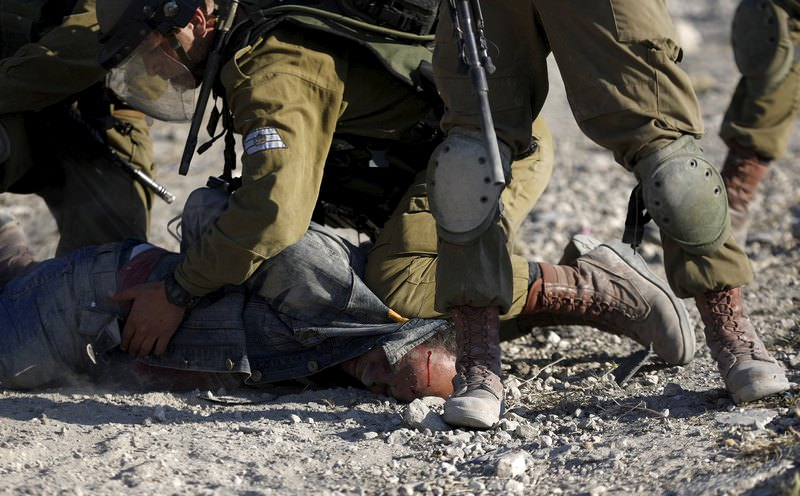 Israeli soldiers detain a Palestinian protester during clashes following a protest against Jewish settlements, in Jalazoun refugee camp, near the West Bank city of Ramallah June 12, 2015 (Reuters Photo)