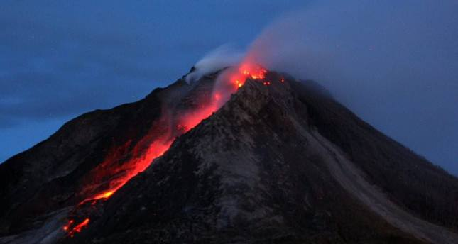 A long exposure picture shows molten lava spilling out from the crater of Mount Sinabung as it is seen from Tiga Serangkai village in Karo, North Sumatra, Indonesia, 13 June 2015 (EPA Photo)