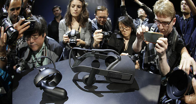 Photographers take pictures of the new Oculus Rift virtual reality headset and touch input device following a news conference Thursday, June 11, 2015, in San Francisco. (AP Photo)