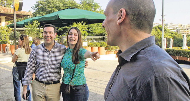 A young woman interrupts the walk of PM Tsipras (L) and Minister of Finance Yanis Varoufakis (R) to take a photograph with them in a park in central Athens.