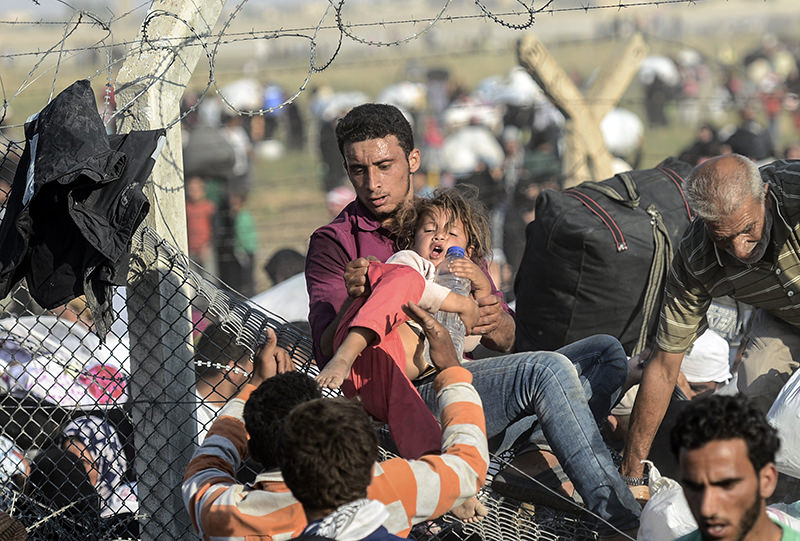 A man carries a girl as Syrians fleeing the war pass through broken down border fences to enter Turkish territory illegally, near the Turkish Akcakale border crossing in the southeastern Sanliurfa province, on June 14, 2015 (AFP Photo)