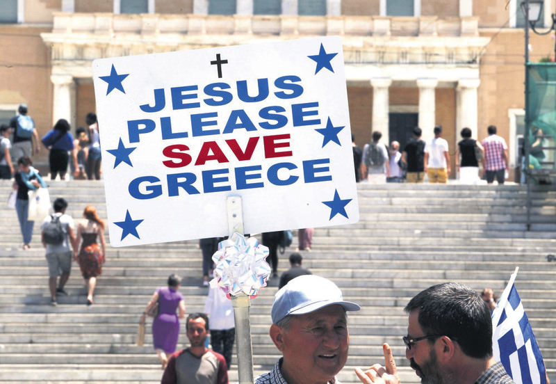 A man holds a placard reading u2018Jesus Please Save Greece' in the main Athens Syntagma Square, opposite the Greek Parliament. Greek PM Tsipras has urged the country's creditors to get realistic a day after weekend negotiations.