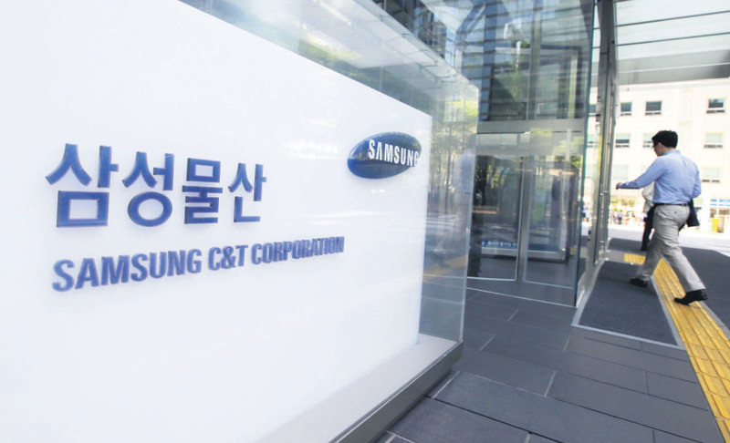 Office workers walk by a logo of Samsung C&T Corp. at its head office in Seoul. Two key Samsung companies are merging in a step toward giving the son of the group's ailing chairman control of the theme parks to smartphones conglomerate.