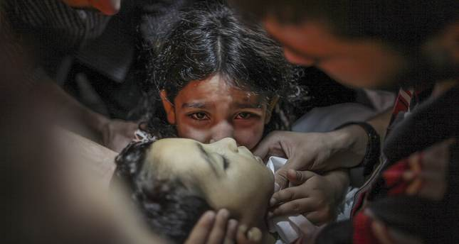 A child killed by Israeli army during a military attack lies in the arms of her sister (Photo by Ali Hasan - Anadolu Agency)