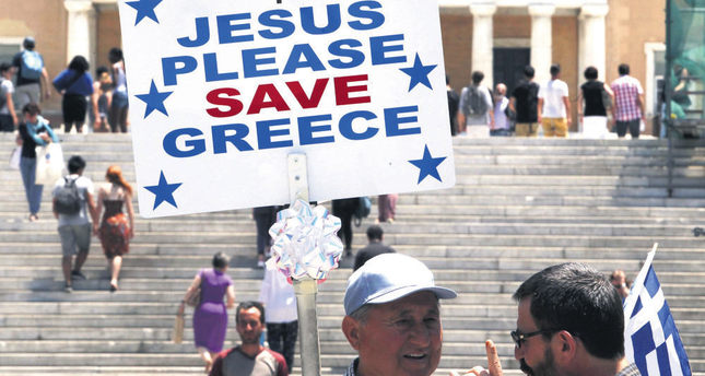 A man holds a placard reading 'Jesus Please Save Greece' in the main Athens Syntagma Square, opposite the Greek Parliament. Greek PM Tsipras has urged the country's creditors to get realistic a day after weekend negotiations.