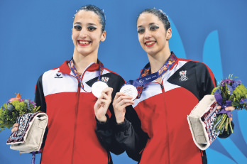 Eirini-Marina, left, and Anna-Maria Alexandri of Austria, celebrate their second place at the final of synchronised swimming.