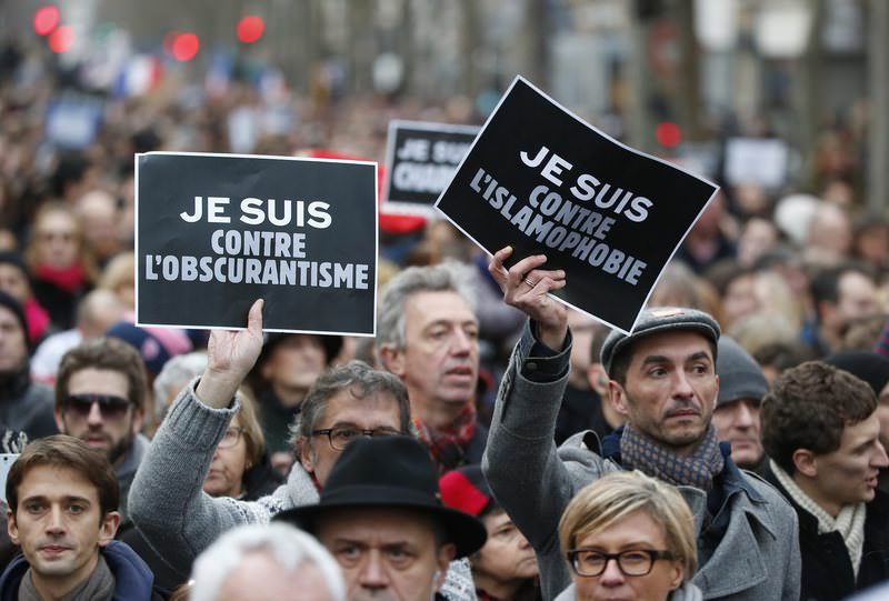 Demonstrators hold posters reading ,I am against obscurantisme,, left, and ,I am against Islamophobia, during a march in Paris, France, Sunday, Jan. 11, 2015 (AP Photo)