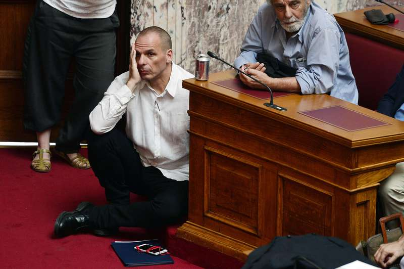 Greek Finance Minister Varoufakis listens to PM Tsipras addressing MP's and ministers at Greek Parliament in Athens (AFP Photo)
