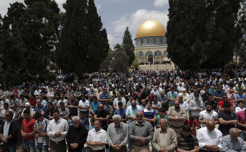 Palestinian worshippers take part in Friday prayers outside the Dome of the Rock at the Al-Aqsa mosque compound in the Old City of Jerusalem on May 22, 2015. (AFP Photo)