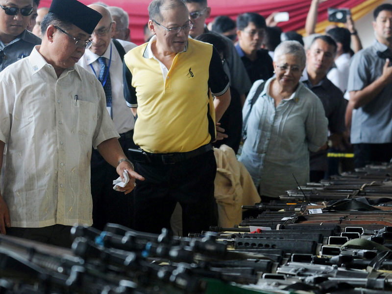 Philippines President Benigno Aquino III, centre, is briefed by Al Haj Murad Ebrahim, left, the leader of Moro Islamic Liberation Front, as he witnesses the handover of weapons (AP Photo)