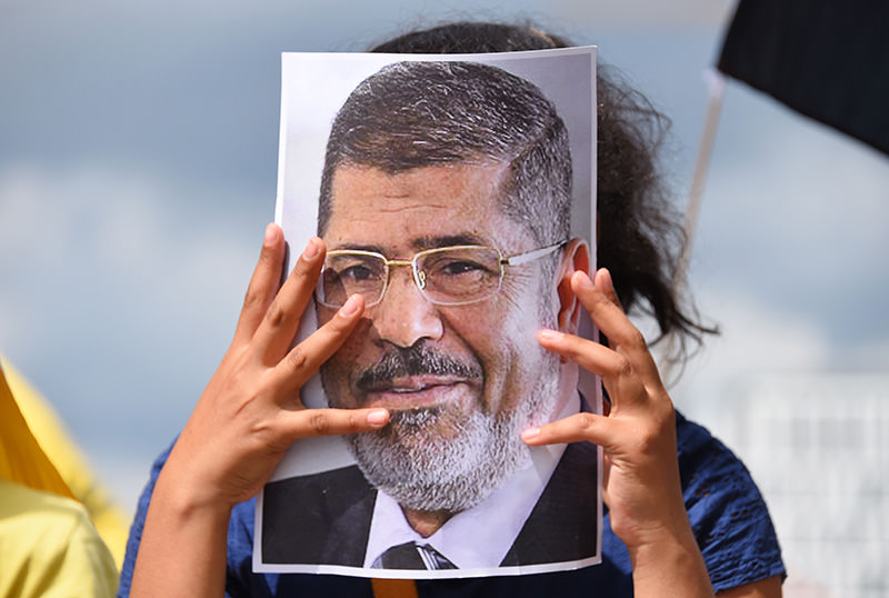 Protester holds a picture of Mohamed Morsi in front of the chancellery in Berlin, Germany, on June 3, 2015 (AFP Photo)