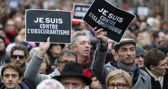 Demonstrators hold posters reading I am against obscurantisme, left, and I am against Islamophobia during a march in Paris, France, Sunday, Jan. 11, 2015 (AP Photo)