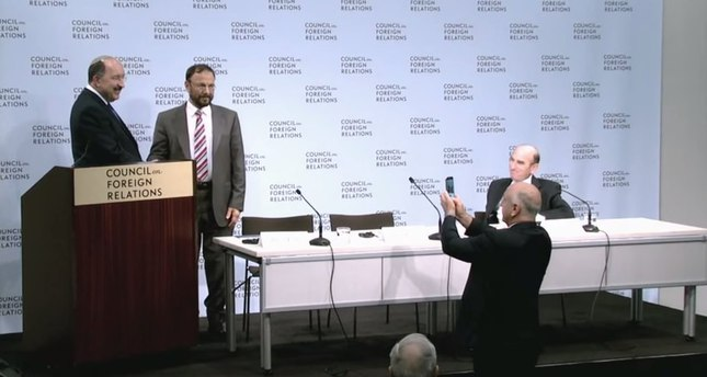 Former Saudi consultant Eshki (right) shaking hands with Israeli diplomat Dore Gold (left) following their speech