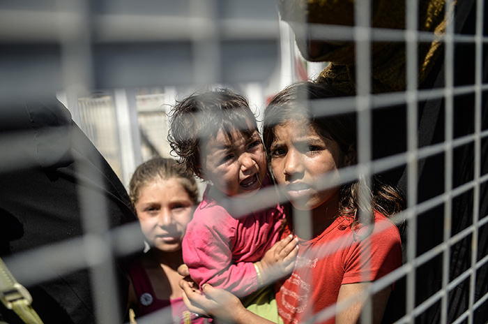 Syrian refugees wait behind a fence prior to go back to the northern Syrian town of Tal Abyad at the Turkish border post of Akcakale, the province of Sanliurfa, on June 17, 2015 (AFP Photo)
