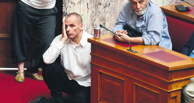 Greek Minister of Finance Yianis Varoufakis (L) listens to Prime Minister addressing Tsipras at the Greek parliament in Athens on June 16. (AFP Photo)