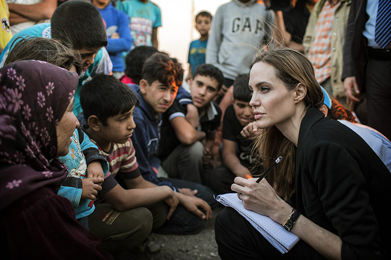 Angelina Jolie taking notes as she speaks with Syrian refugees in a Jordanian military camp based near the Syria-Jordan border on June 18, 2013 (AP Photo)