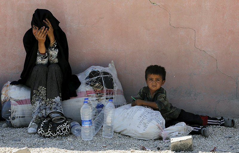 Syrian refugee woman from the northern Syrian town of Tel Abyad and her child wait while spending the day in Aku00e7akale, in u015eanlu0131urfa province, Turkey, June 18, 2015 (REUTERS Photo)