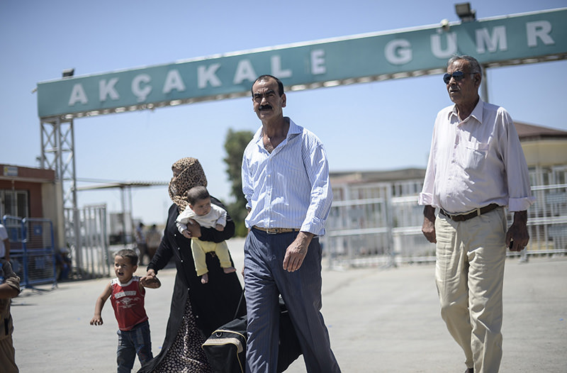 Syrian refugees walk along the road that leads to the Aku00e7akale border gate as they wait to return to their home in the northern Syrian town of Tel Abyad, in u015eanlu0131urfa province, on June 18, 2015 (AFP Photo)