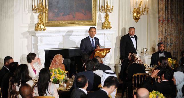 President Barack Obama stands at the podium and speaks as he hosts an Iftar dinner celebrating Ramadan in the State Dining Room of the White House, Thursday, July 25, 2013, in Washington.