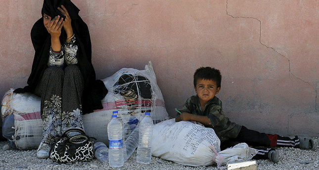 Syrian refugee woman from the northern Syrian town of Tel Abyad and her child wait while spending the day in Akçakale, in Şanlıurfa province, Turkey, June 18, 2015 (REUTERS Photo)