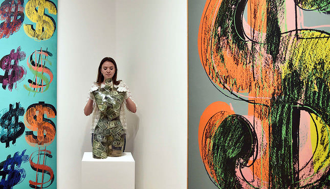 A Christie's employee poses with 'Venus aux dollars' by Arman, of a private collection of twenty one works inspired by the US dollar, at Sotheby's auction house in London June 8, 2015 (Reuters Photo)