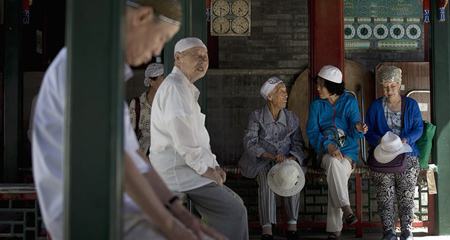 Chinese Muslim chat outside the worship hall on the first day of the Muslim holy month of Ramadan at the Niujie Mosque, the oldest and largest mosque in Beijing, China Thursday, June 18, 2015 (AP Photo)