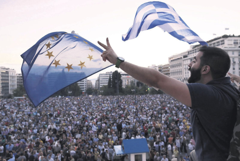 Demonstrators wave European and Greek flags as they stand in front of parliament in Athens on June 18.