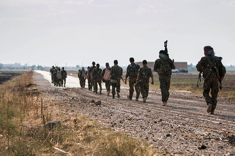 Syrian Kurdish YPG militia fighters walk carrying their weapons towards Tel Abyad of Raqqa governorate after they said they took control of the area from ISIS on June 15, 2015 (Reuters Photo)