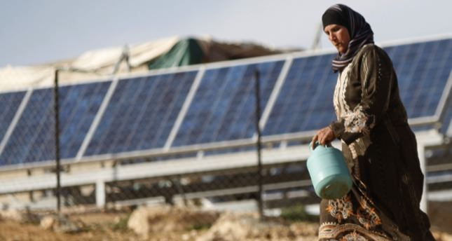 A Gazan woman walks past solar panels in Gaza City.