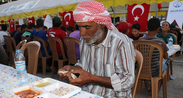 Syrian man breaks his fast at an iftar dinner hosted by Akçakale Municipality (AA Photo)