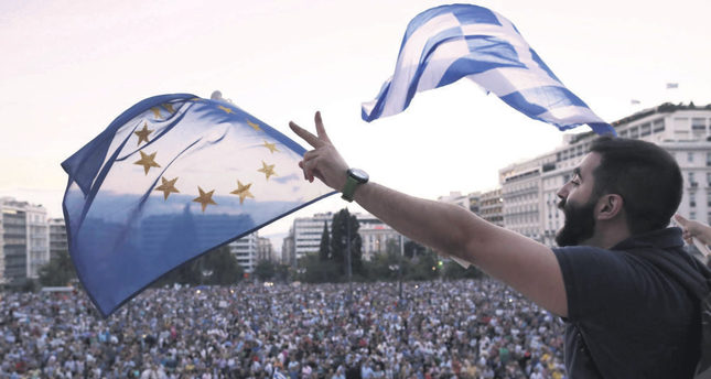 Demonstrators wave European and Greek flags as they stand in front of parliament in Athens on June 18. (EPA Photo)