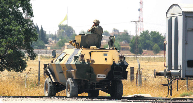A Turkish soldier on an armoured personnel carrier watches as in the background a flag of the YPG is raised over the city of Tal Abyad on Tuesday.