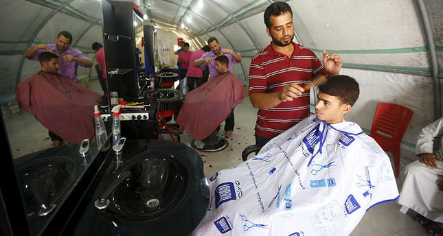A hairdresser cuts the hair of a customer at Suleymansah refugee camp in Akcakale in Sanliurfa province, Turkey, June 11, 2015 (Reuters Photo)